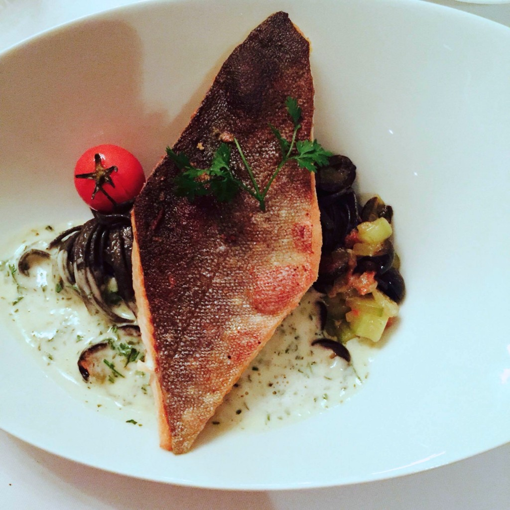 Frischer Fisch auf Olivenbett  und schwarzen Nudeln